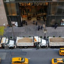 Trump and Clinton's location surrounded with dump trucks of sand